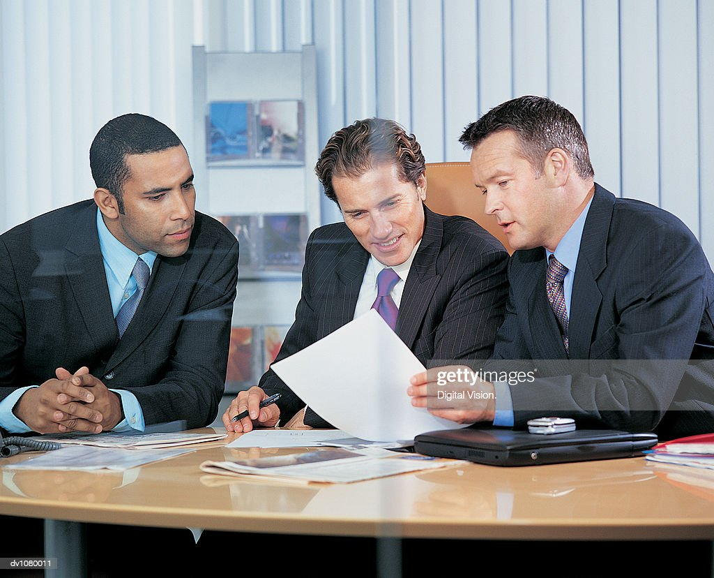 Three Business Executives Sitting at a Table and Discussing an Application Form After an Interview