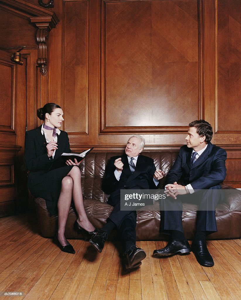 Three Business Executives Sitting on a Leather Sofa Having a Discussion : Stock Photo