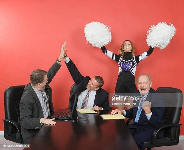Three business men at conference table, two doing high five, teenage (14-15) cheerleader in background