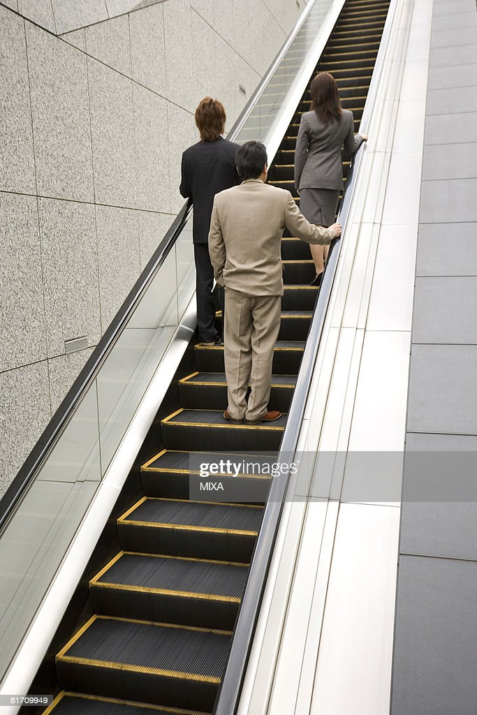 Three business people ascending escalator : Stock Photo
