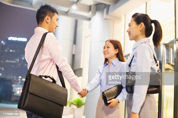 three business people handshaking outside the office