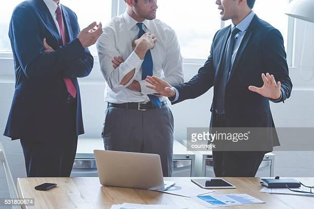 Drei Geschäftsleute eine Debatte.