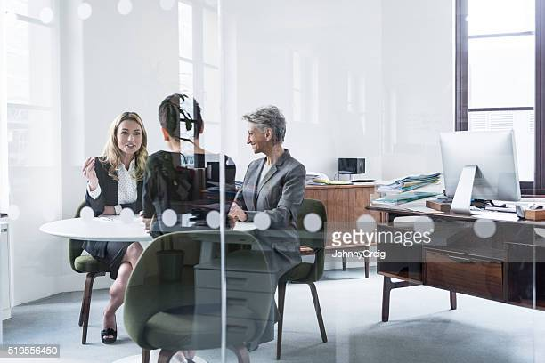 Three business people having meeting behind glass partition