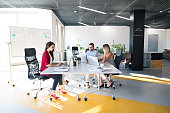 Three business people in the workplace. Two women and man sitting in the office working together.