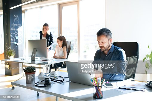 Three business people in the office working together. : Stock Photo