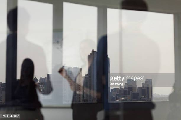Three business people standing and looking at a white board on the other side of a glass wall