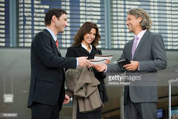 Three business people standing at the airport.