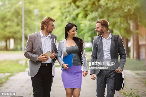 Three business people taking a walk in park.