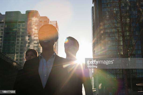 Three business people walking down a city street with sunlight at their back, lens flare