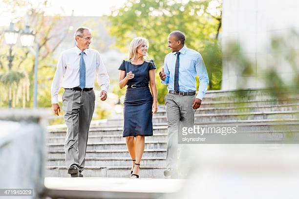 Tre uomini d'affari a piedi all'aperto.