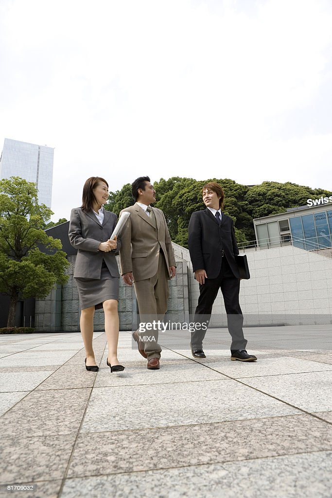 Three business people walking : Stock Photo