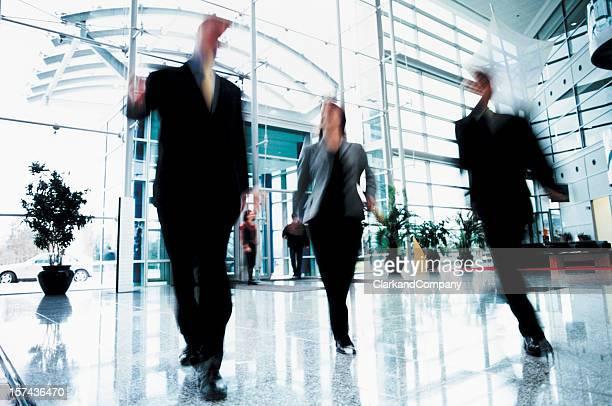 Tre uomini d'affari camminare rapidamente s'Office ingresso