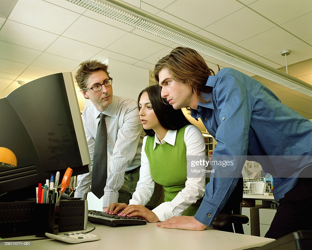 Three business people working together in front of computer : Stock Photo