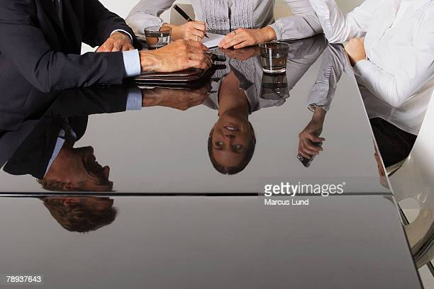 Three business people's reflection in a table.