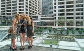 Three business women share text, gossip