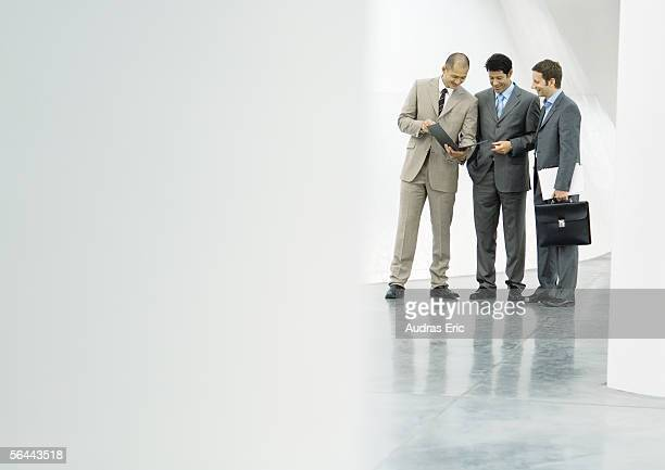 Three businessman standing in lobby, looking at file