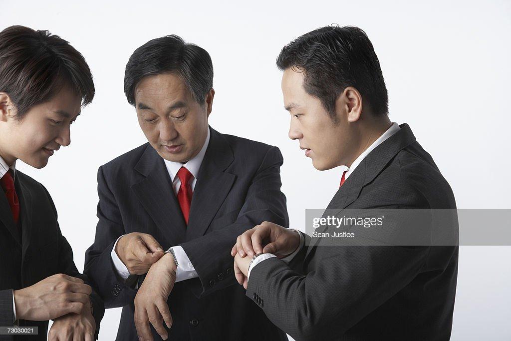 Three businessman synchronizing watches : Stock Photo