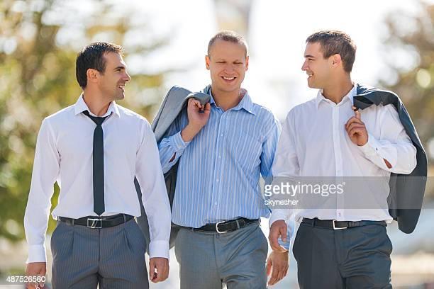 Trois Homme d'affaires marchant le long de la rue et de la communication.