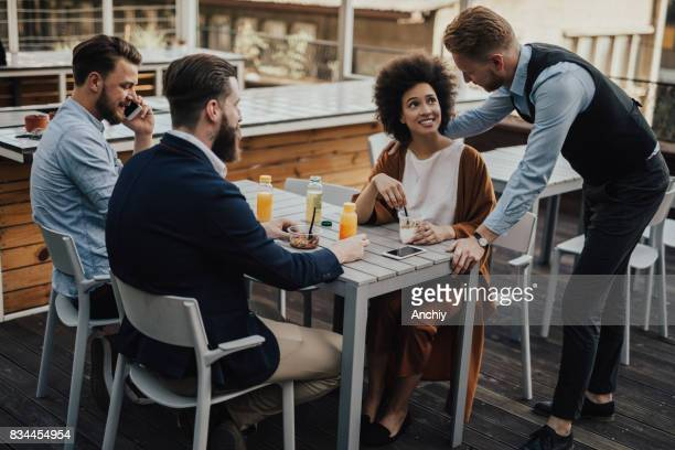 Three businessmen and a businesswoman meet in a bar after work.