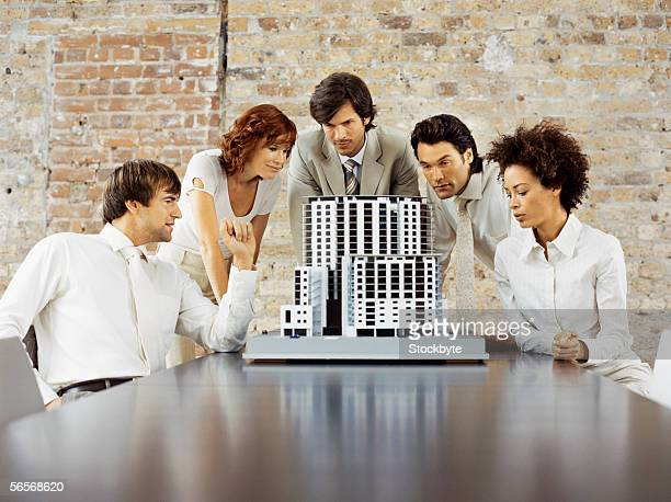 three businessmen and two businesswomen looking at an architectural model