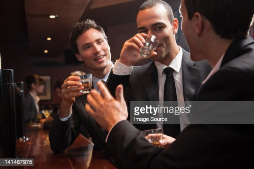 Three businessmen drinking at a bar : Stock Photo