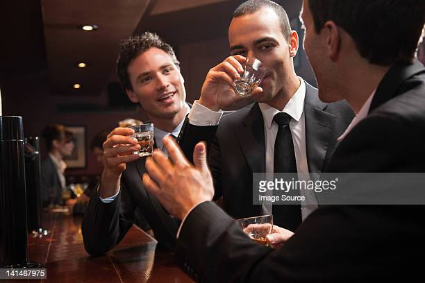 Three businessmen drinking at a bar