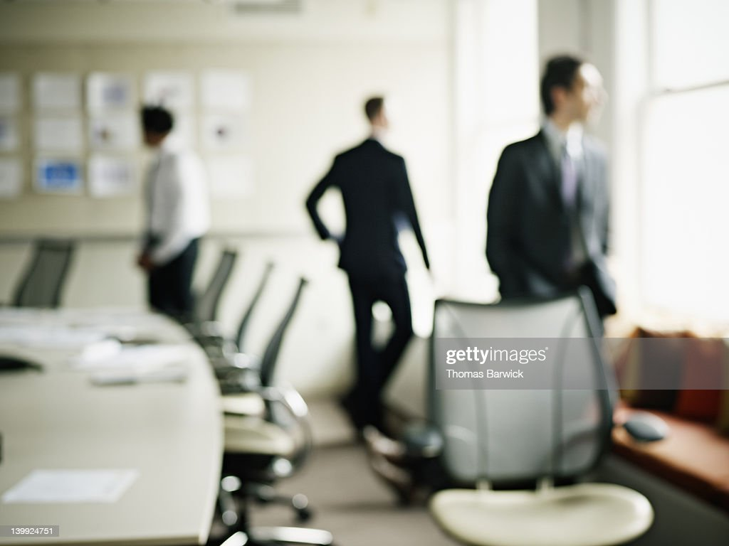 Three businessmen in conference room out of focus