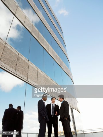 Three Businessmen in Discussion Standing Outside an Office Building : Stock Photo