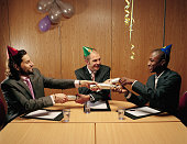 Three businessmen in party hats pulling crackers across table
