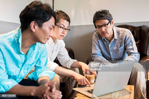 Three businessmen looking at a laptop