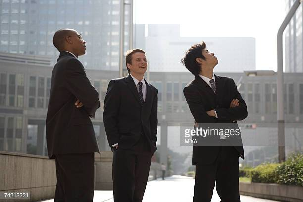 Three businessmen looking up