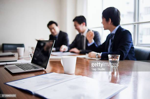 Three businessmen meeting in a conference room.