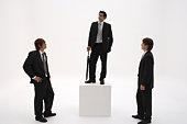 Three businessmen, one standing on winners podium, holding umbrella