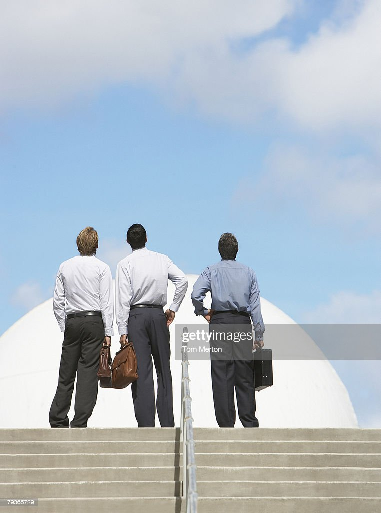 Three businessmen outdoors at top of staircase looking up : Stock Photo