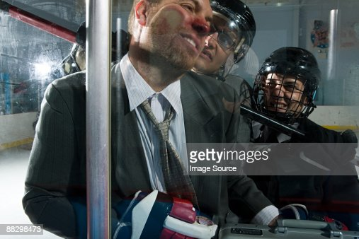 Three businessmen playing ice hockey : Stock Photo