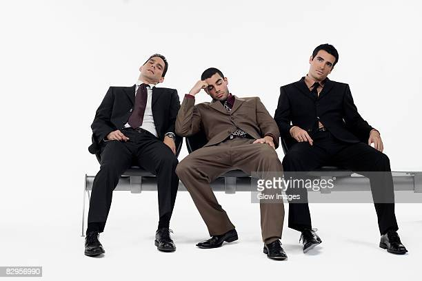 Three businessmen sitting a bench and looking stressed