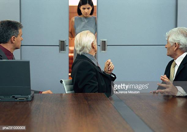 Three businessmen sitting at conference table,  businesswoman entering door, portrait