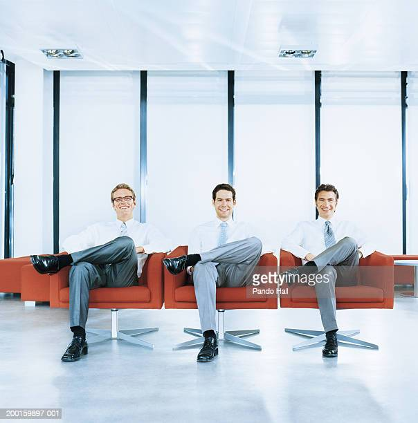 Three businessmen sitting in armchairs, smiling, portrait