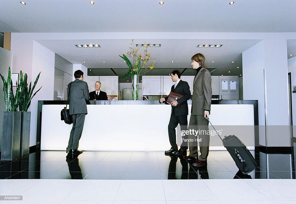 Three businessmen standing at reception desk in hotel lobby