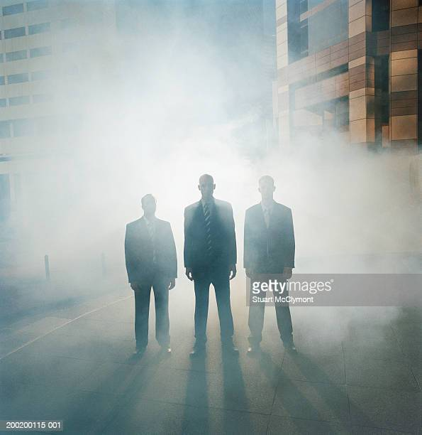 Three businessmen standing in a row surrounded by mist