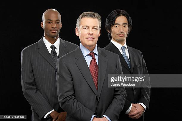 Three businessmen standing together, smiling, portrait