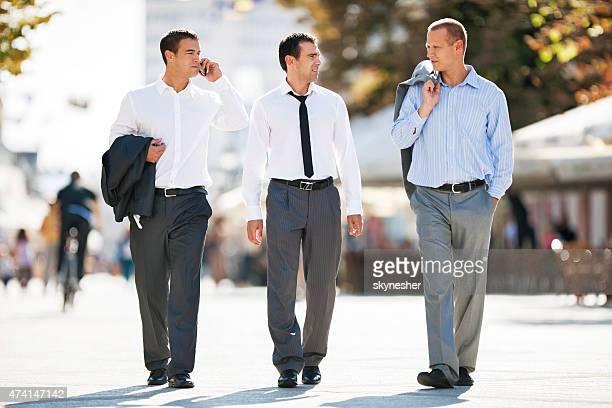 Trois hommes d'affaires marchant le long de la rue et de la communication.