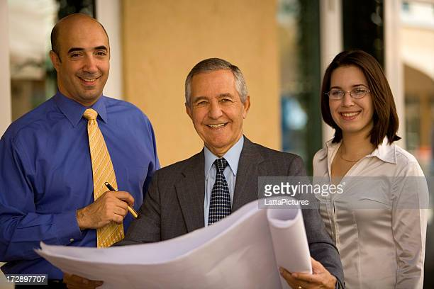 Three businesspeople holding architectural plans