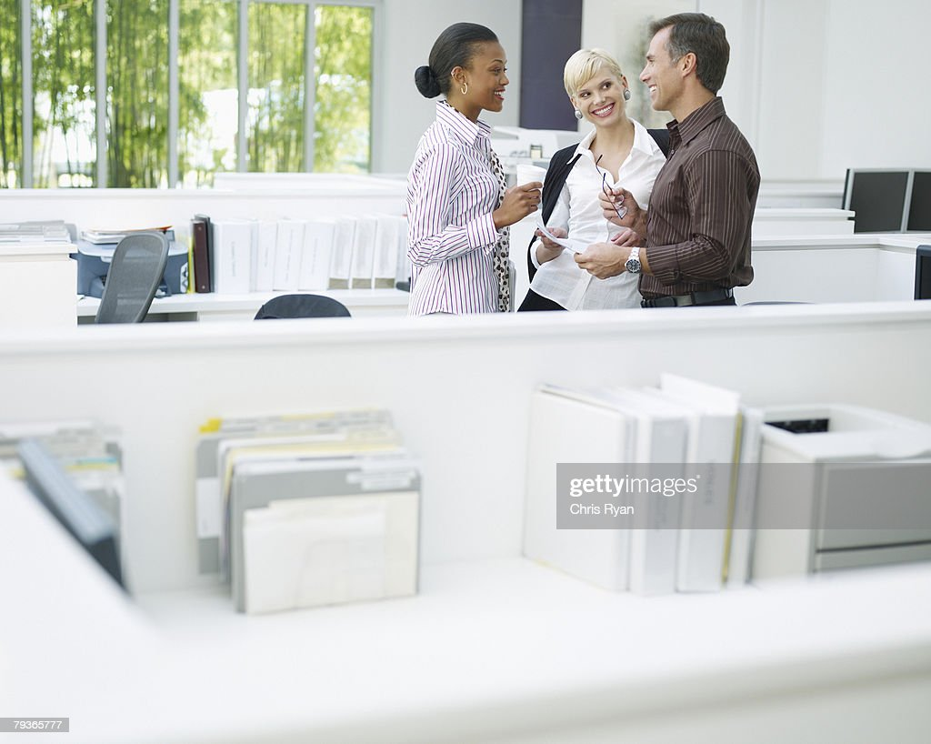 Three businesspeople in an office talking : Stock Photo