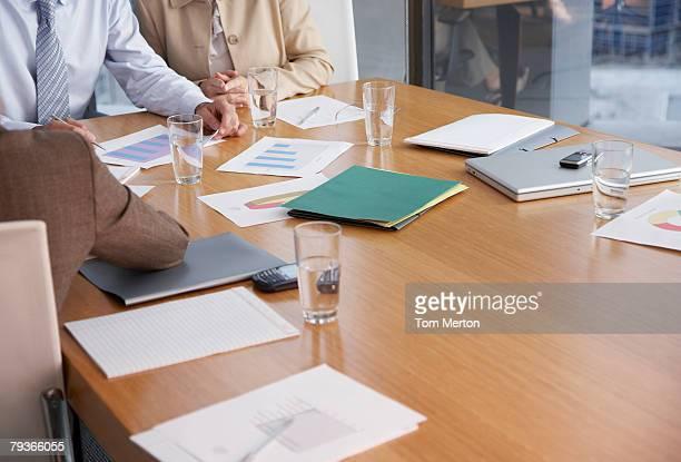 Tres hombres de negocios en la sala de juntas con papeleo y computadora portátil