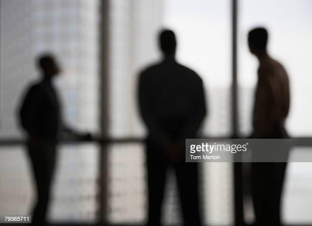 Tre uomini d'affari in corridoio dalle grandi finestre