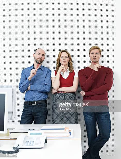 three businesspeople in office, thinking