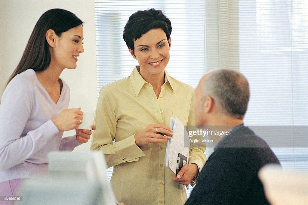 Three businesspeople talking : Stock Photo