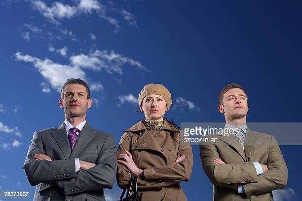 Three businesspeople with crossed arms standing side by side