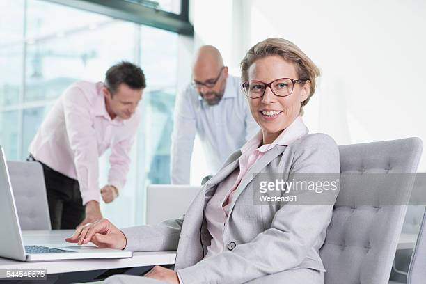 Three businesspeople with laptop in conference room